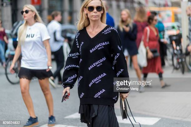 A guest wearing a black Balenciaga sweater with v neck outside Baum Und Pferdgarten on August 10 2017 in Copenhagen Denmark
