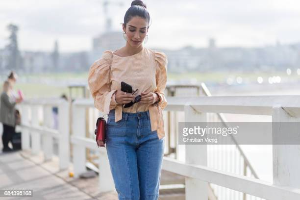 A guest wearing a blouse denim jeans red Bulgari bag outside Ten Pieces at day 5 during MercedesBenz Fashion Week Resort 18 Collections at Icebergs...