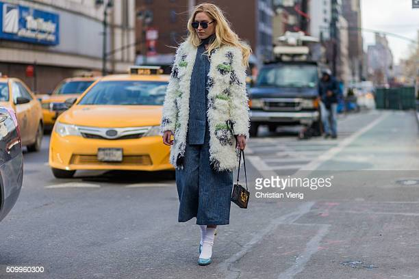 A guest wearing a blue denim jumpsuit turquoise heels with white socks a small brown Louis Vuitton bag and a white green fluffy fur coat seen outside...