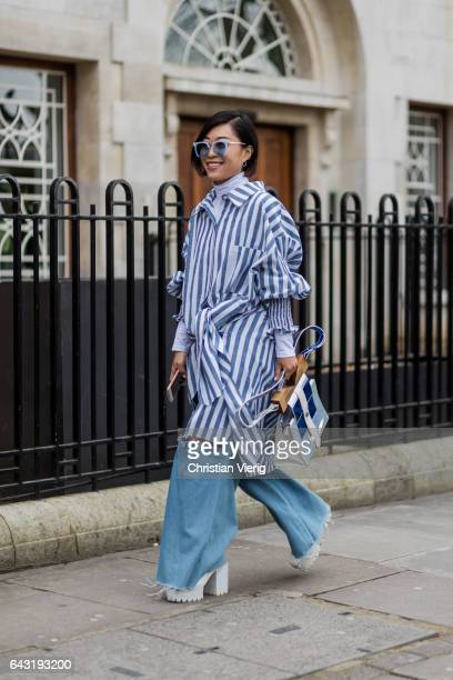 A guest wearing a blue white striped button shirt ripped denim jeans outside Anya Hindmarch on day 3 of the London Fashion Week February 2017...