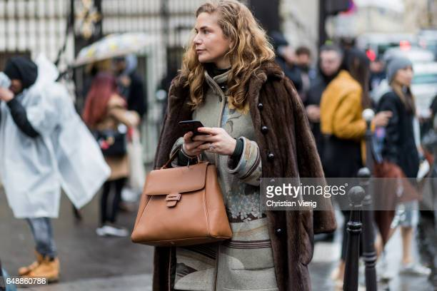 A guest wearing a brown fur coat outside Giambattista Valli on March 6 2017 in Paris France