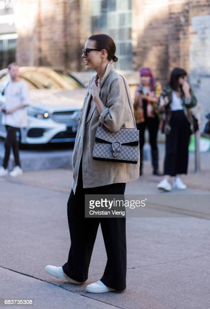 A guest wearing a brown jacket Gucci bag black jumpsuit at day 3 during MercedesBenz Fashion Week Resort 18 Collections at Carriageworks on May 16...
