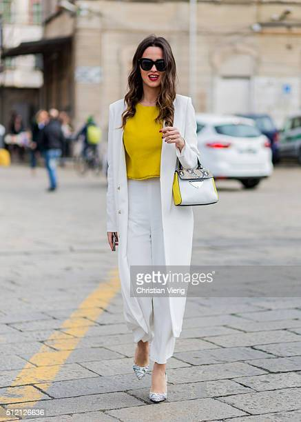 A guest wearing a Coccinelle bag white pants and coat and yellow top seen outside Gucci during Milan Fashion Week Fall/Winter 2016/17 on February 24...