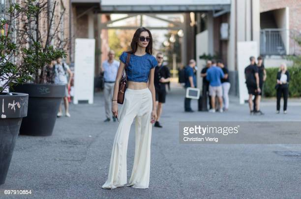 A guest wearing a cropped top creme wide leg pants is seen outside Malibu 1992 during Milan Men's Fashion Week Spring/Summer 2018 on June 19 2017 in...