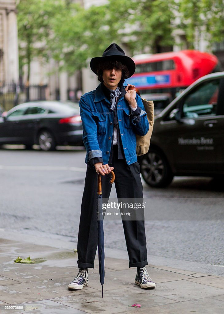 A guest wearing a denim jacket black pants and hat and Converse shoes outside Christopher Raeburn during The London Collections Men SS17 on June 12...