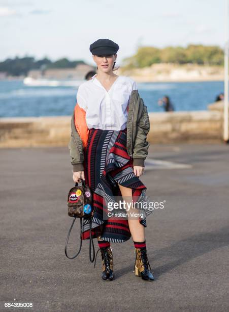 A guest wearing a flat cap bomber jacket Louis Vuitton backpack ruffled skirt and boots outside Dyspnea at day 5 during MercedesBenz Fashion Week...