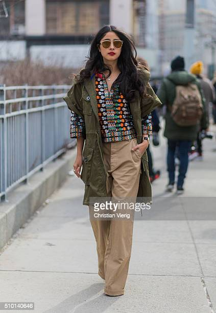 A guest wearing a green parka jacket and beige wide pants seen outside Jason Wu during New York Fashion Week Women's Fall/Winter 2016 on February 12...
