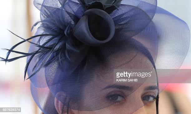 A guest wearing a hat arrives at the Meydan Racecourse to attend the Dubai World Cup day horse racing event on March 25 2017 in Dubai / AFP PHOTO /...