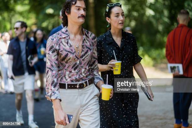 A guest wearing a mustache pink silk dress with floral print and a guest wearing a black dress and drinking juice to go outside Balenciaga during...