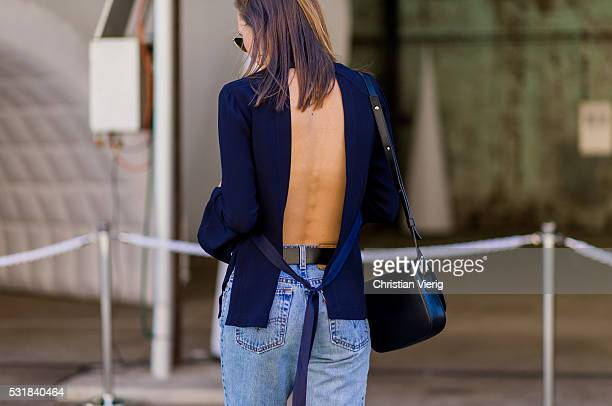 A guest wearing a navy backless shirt and Levis jeans outside By Johnny at MercedesBenz Fashion Week Resort 17 Collections at Carriageworks on May 17...