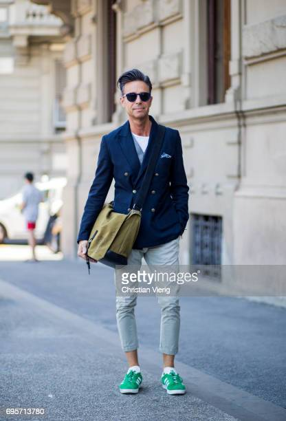 A guest wearing a navy blazer jacket weekender bag is seen during Pitti Immagine Uomo 92 at Fortezza Da Basso on June 13 2017 in Florence Italy