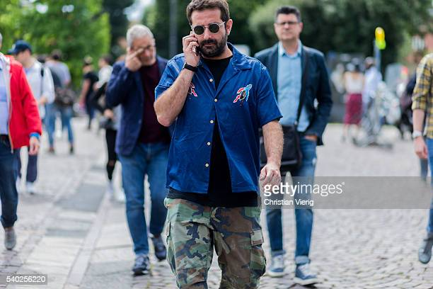 A guest wearing a navy button shirt and military pants during Pitti Uomo 90 on June 14 in Florence Italy