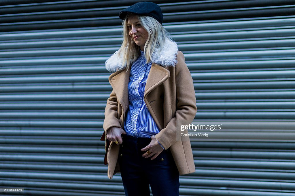 A guest wearing a navy flat cap a blue white button shirt and a beige wool coat with fur collar seen outside Eudon Choi during London Fashion Week AW16 on February 19, 2016 in London, England, United Kingdom.