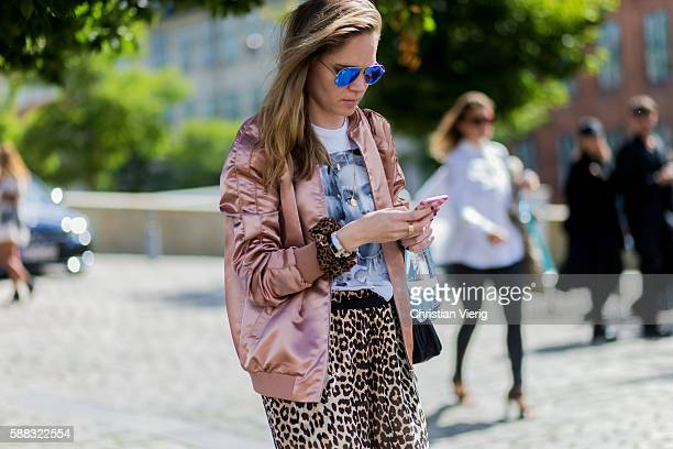 A guest wearing a pink bomber jacket and pants with leo print outside Freya Dalsjo during the first day of the Copenhagen Fashion Week Spring/Summer...