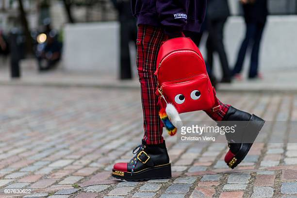 A guest wearing a red Anya Hindemarch backpack and Prada shoes outside Preen during London Fashion Week Spring/Summer collections 2017 on September...