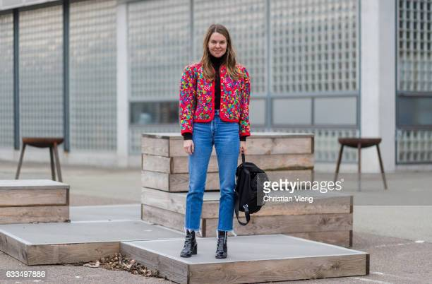 A guest wearing a red blazer jacket black backpack cropped denim jeans black ankle boots outside Tonsure at the Copenhagen Fashion Week Autumn/Winter...