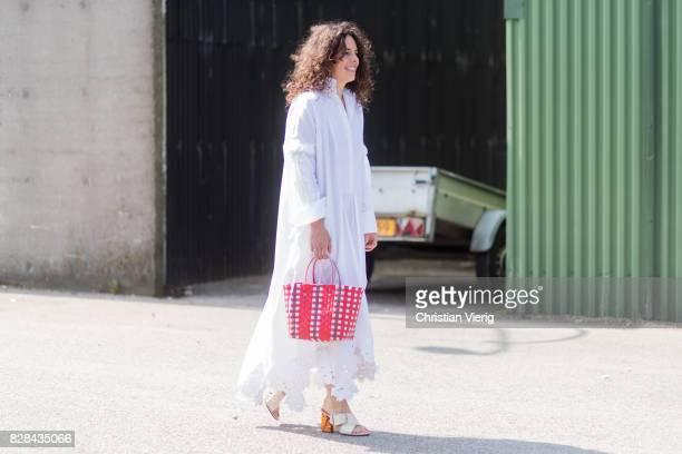 A guest wearing a red bucket bag white dress with long sleeves outside By Malene Birger on August 09 2017 in Copenhagen Denmark