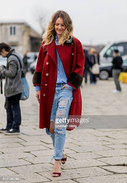 A guest wearing a red coat and blue ripped jeans seen outside Gucci during Milan Fashion Week Fall/Winter 2016/17 on February 24 2016 in Milan Italy