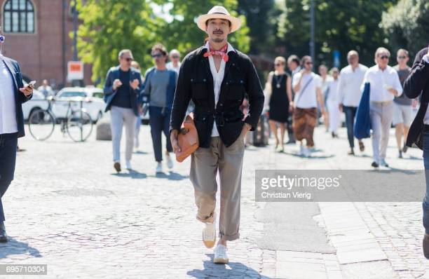 A guest wearing a straw hat red scarf black jacket brown clutch grey pants is seen during Pitti Immagine Uomo 92 at Fortezza Da Basso on June 13 2017...
