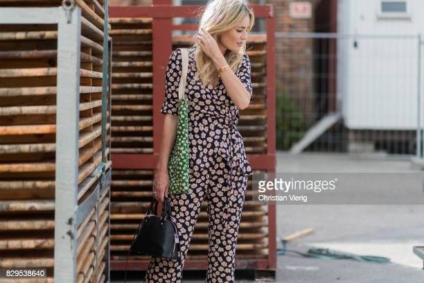 A guest wearing a suit with floral print outside Ganni on August 10 2017 in Copenhagen Denmark