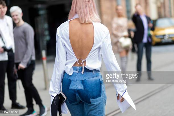 A guest wearing a top white backless top Vetements denim jeans at day 5 during MercedesBenz Fashion Week Resort 18 Collections at Carriageworks on...
