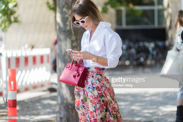 A guest wearing a white blouse skirt with floral print outside Munthe on August 09 2017 in Copenhagen Denmark