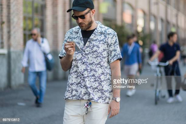 A guest wearing a white button shirt with print and short sleeves cap is seen outside Malibu 1992 during Milan Men's Fashion Week Spring/Summer 2018...