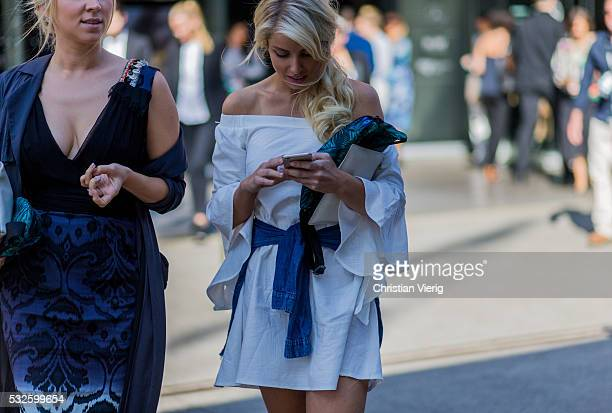 A guest wearing a white off shoulder dress and denim jacket knotted around her hips at MercedesBenz Fashion Week Resort 17 Collections at...