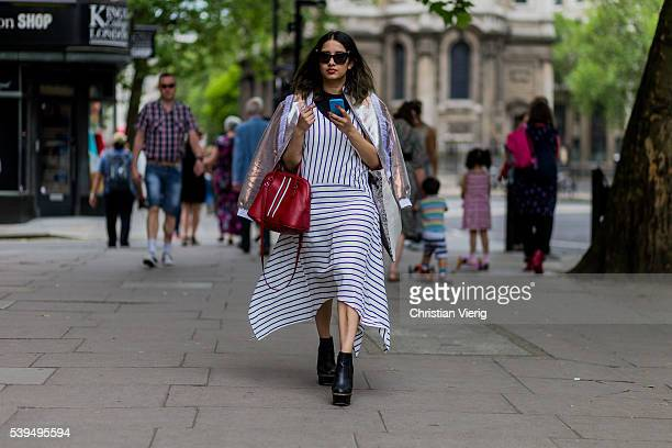 A guest wearing a white striped dress and black boots and red bag outside Nasir Mazhar during The London Collections Men SS17 on June 11 2016 in...