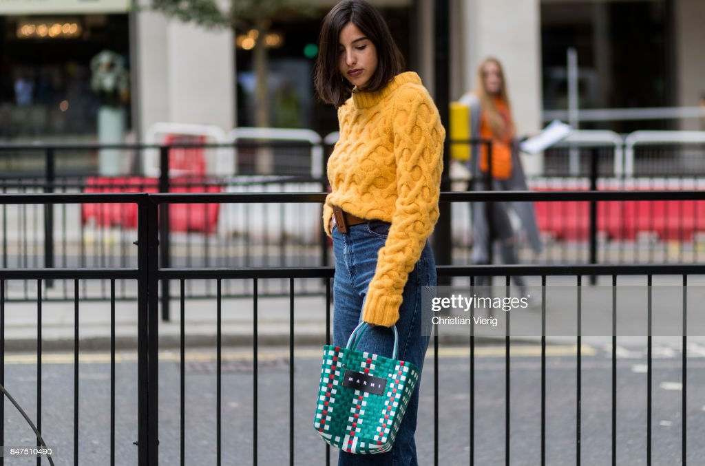 A guest wearing a yellow knit, Marini bag, denim jeans during London Fashion Week September 2017 outside Eudon Choi on September 15, 2017 in London, England.