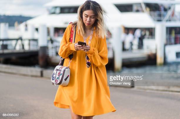 A guest wearing a yellow orange dress with long sleeves outside Dyspnea at day 5 during MercedesBenz Fashion Week Resort 18 Collections at Sydney...