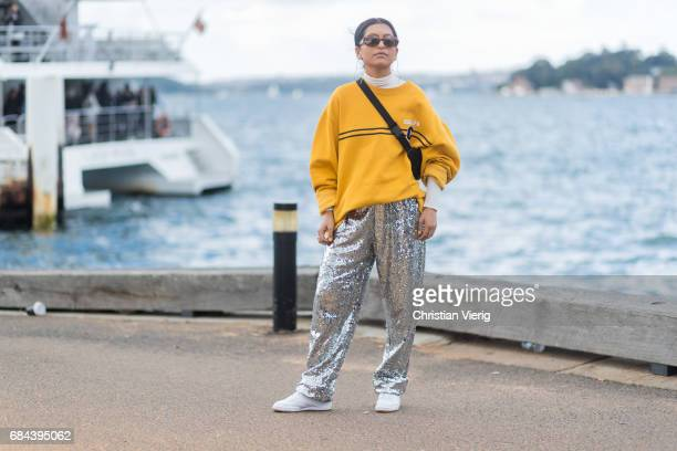 A guest wearing a yellow sweater silver pants outside Dyspnea at day 5 during MercedesBenz Fashion Week Resort 18 Collections at Sydney Opera House...