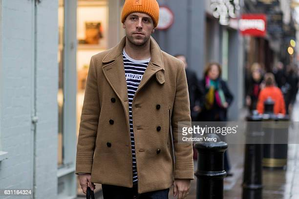 A guest wearing Acne beanie camel jacket during London Fashion Week Men's January 2017 collections at YMC on January 7 2017 in London England