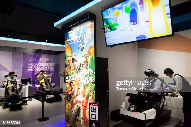 A guest wearing an HTC Corp Vive virtual reality headset tries the Mario Kart Arcade GP VR attraction right at the VR Zone Shinjuku theme park...