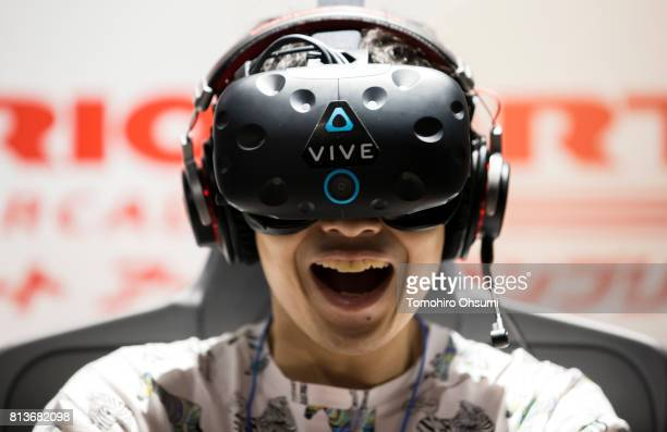 A guest wearing an HTC Corp Vive virtual reality headset tries the Mario Kart Arcade GP VR attraction at the VR Zone Shinjuku theme park operated by...