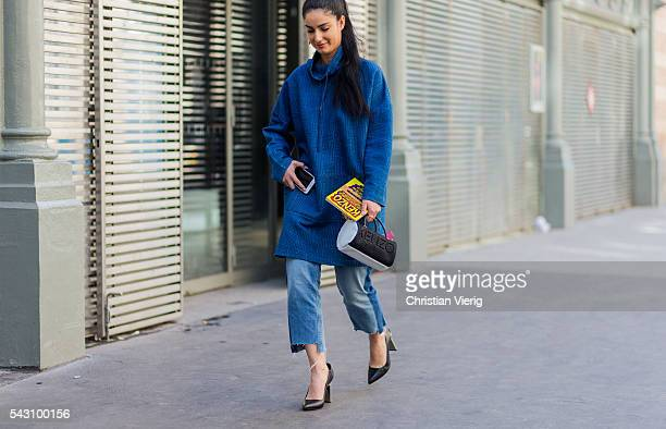 A guest wearing an oversized blue jumper Vetements jeans and Kenzo bag outside during the Paris Fashion Week Menswear Spring/Summer 2017 on June 25...