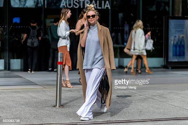 A guest wearing an oversized brown coat a grey sweater and wide white pants outside C Meo Collective at MercedesBenz Fashion Week Resort 17...