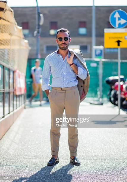 A guest wearing beige pants striped button shirt is seen during Pitti Immagine Uomo 92 at Fortezza Da Basso on June 13 2017 in Florence Italy