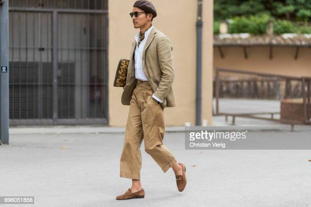 A guest wearing beret brown pants clutch blazer is seen during Pitti Immagine Uomo 92 at Fortezza Da Basso on June 14 2017 in Florence Italy