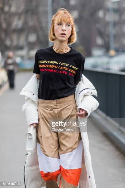 A guest wearing black tshirt with print white down feather coat brown beige pants outside Fendi during Milan Fashion Week Fall/Winter 2017/18 on...