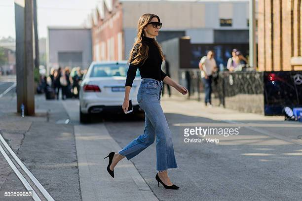 A guest wearing blue denim jeans and heels and a black jumper at MercedesBenz Fashion Week Resort 17 Collections at Carriageworks on May 19 2016 in...