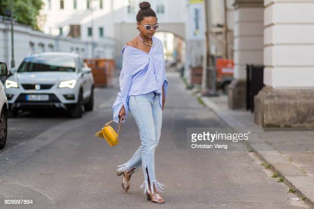 A guest wearing blue white striped button shirt yellow Moschino bag ripped denim jeans Gucci mules during the MercedesBenz Fashion Week Berlin...