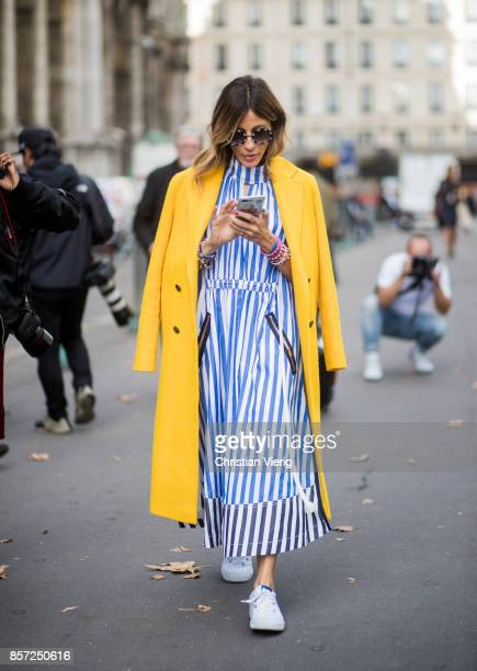 A guest wearing blue white striped dress yellow coat seen outside Thom Browne during Paris Fashion Week Spring/Summer 2018 on October 3 2017 in Paris...