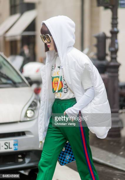 A guest wearing hooded down feather jacket Gucci shirt and jogger pants outside Acne on March 4 2017 in Paris France