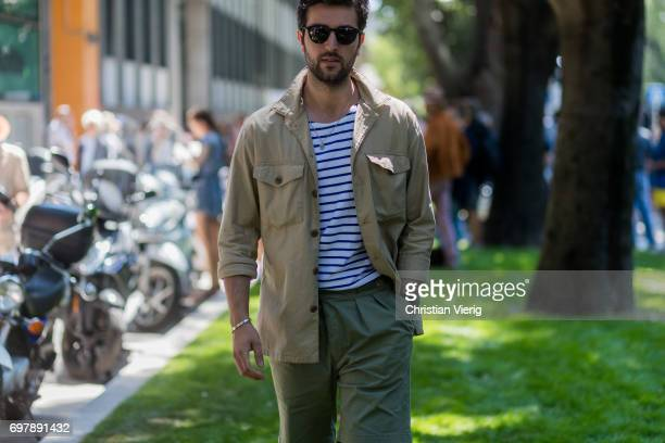 A guest wearing khaki button shirt striped tshirt olive pants is seen outside Armani during Milan Men's Fashion Week Spring/Summer 2018 on June 19...