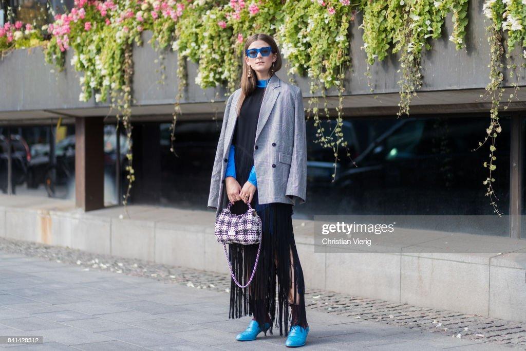 A guest wearing Stella Mc Cartney bag, skirt with fringes, grey blazer jacket outside House of Dagmar on August 31, 2017 in Stockholm, Sweden.