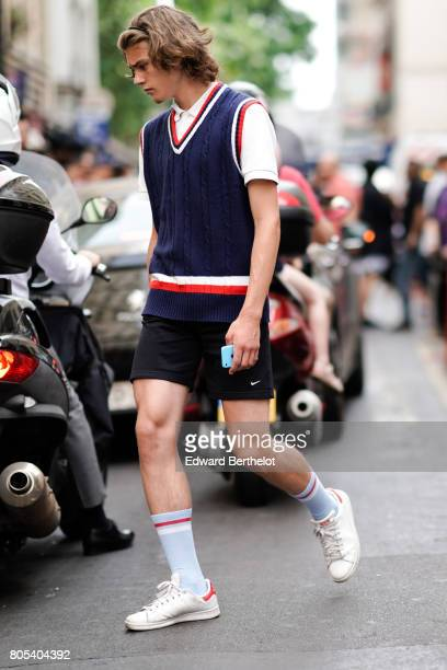 A guest wears a a blue red and white sleeveless pull over a white polo shirt black shorts light blue socks white sneakers after Yohji Yamamoto show...