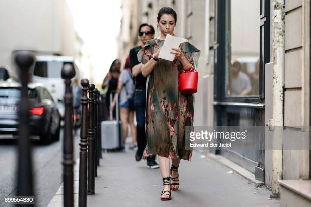 A guest wears a a ruffled flower print dress a red bag and sandals outside the OAMC show during Paris Fashion Week Menswear Spring/Summer 2018 on...