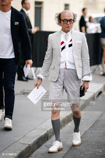 A guest wears a a striped blazer jacket striped shorts knee high gray socks white sneakers outside the Valentino show during Paris Fashion Week...