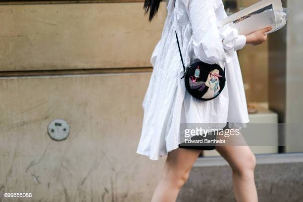 A guest wears a a white blouse and a bag with an embroidered picture representing Alice in Wonderland outside the OAMC show during Paris Fashion Week...